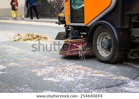 Street sweeper machine cleaning the street after a carnival party. Selective focus. - stock photo