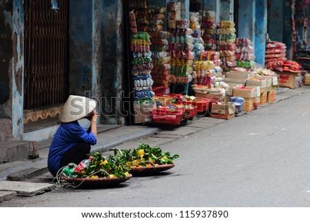 Street vendor in Vietnam selling fruit at a corner in Hanoi. - stock photo
