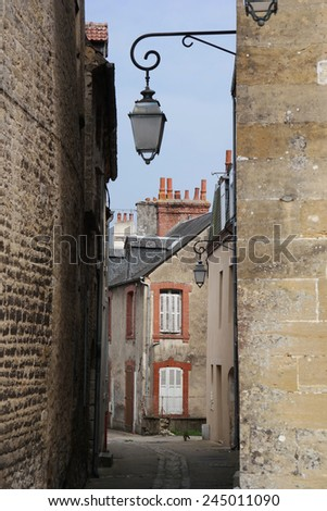 Street view into a characteristic bystreet with lanterns in Carentan, Normandy, France - stock photo