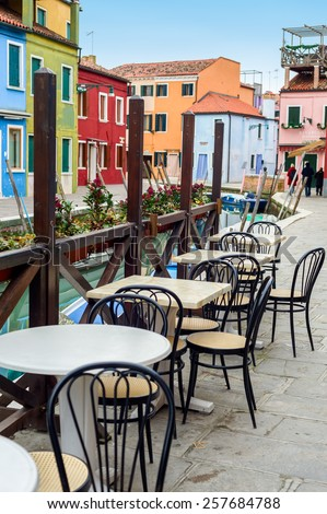 Street view of a cafe terrace with empty tables and chair on the famous island Burano, Venice, Italy. - stock photo