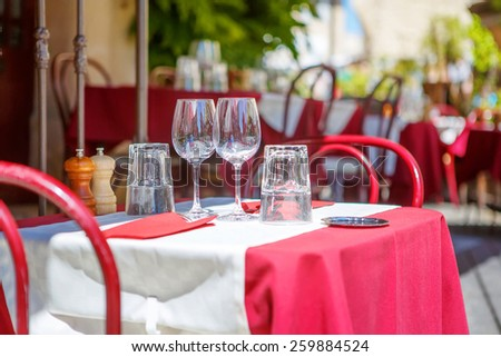 Street view of a cafe terrace with empty tables and chairs, Provence, France. Table set for a lunch or dinner, with glassware, vine glasses - stock photo