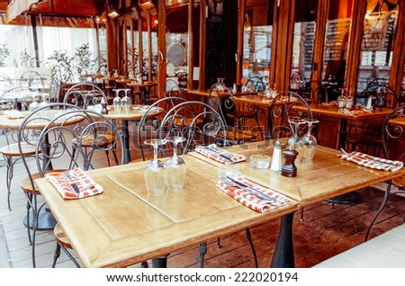 Street view of a coffee terrace with tables and chairs in europe - stock photo