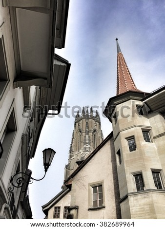 Street view of the St-Nicolas cathedral behind traditional houses in Fribourg (Switzerland)