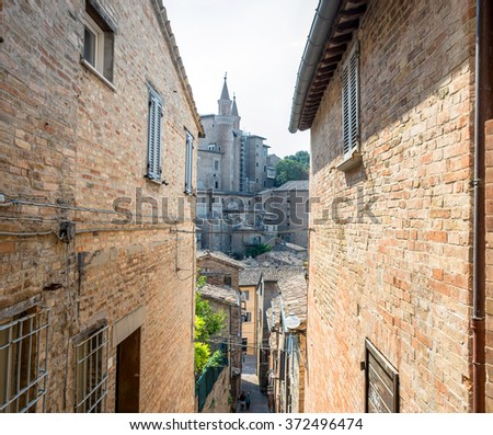 street view with skyline in Urbino, Italy. The historic center of Urbino was declared a Unesco World Heritage site and represents the apex of Renaissance architecture - stock photo