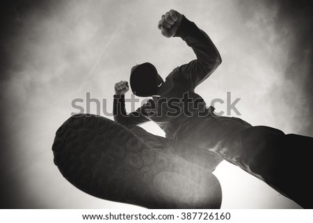 Street violence, victim being punched and mugged by aggressive violent man in hooded jacket, monochromatic image - stock photo