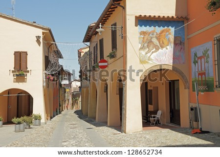 street with arcades and murals in Dozza , Italian small town known for its festival of the painted wall, which takes place every two years. Emilia-Romagna, Italy, Europe - stock photo