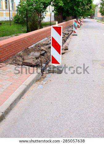 Street with demolished footpath and enclosure from warning signs         - stock photo
