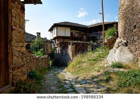 Street with old houses in Kovatchevitsa village, Bulgaria - stock photo