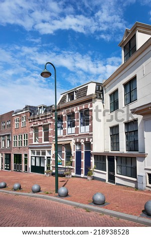 Street with row of renovated houses with green lantern, Gouda, The Netherlands - stock photo