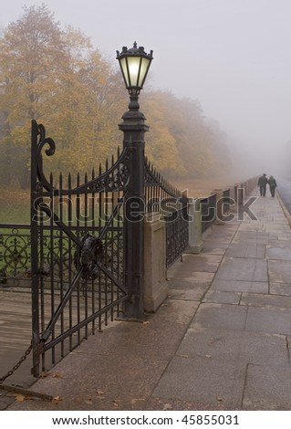 streetlight at the gate in fog - stock photo