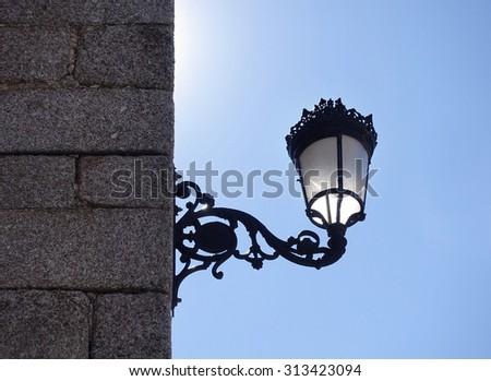 Streetlight black color backlit on a blue sky - stock photo