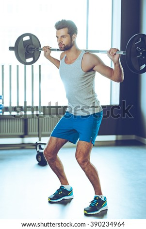 Strength and concentration. Full Length of young handsome man in sportswear lifting barbell at gym - stock photo
