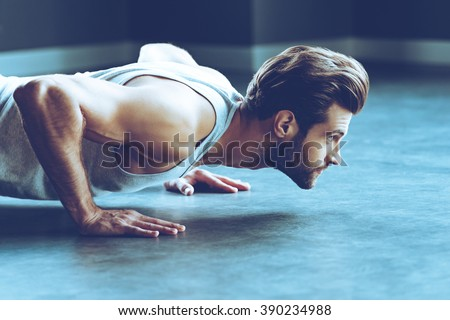 Strength and motivation. Side view of young handsome man in sportswear doing push-up at gym - stock photo