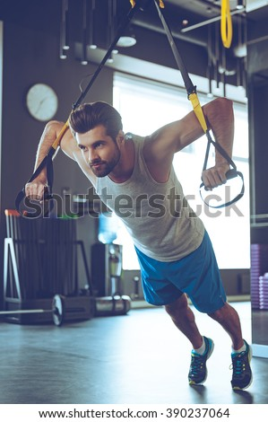 Strength and power. Full-length of young man in sportswear exercising at gym - stock photo
