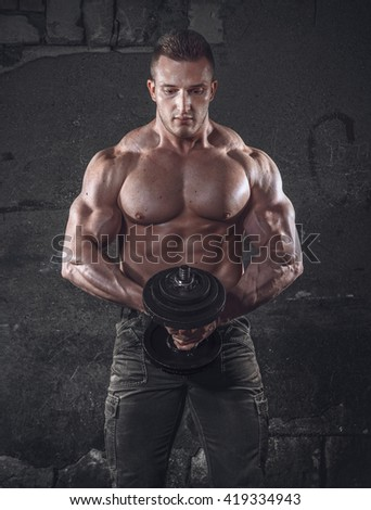 Strength bodybuilder with weight posing against grunge wall, dramatic light