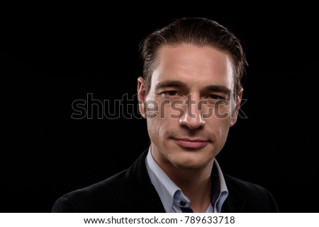 Strength. Portrait of calm fashionable young entrepreneur is standing and looking at camera seriously. Isolated background