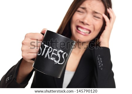 Stress at work concept. Business woman stressed being to busy. Businesswoman in suit holding head drinking coffee creating more stress. Mixed race Asian Caucasian female isolated on white background. - stock photo
