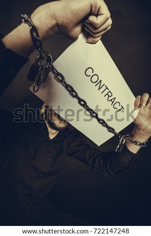 Stress at work, no freedom, pursuit of money concept. Scared man with chained hands holding contract, studio shot on dark, grunge background