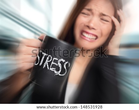 Stress - business person stressed at office. Business woman holding coffee cup with STRESS written. Overworked and over caffeinated female businesswoman. - stock photo