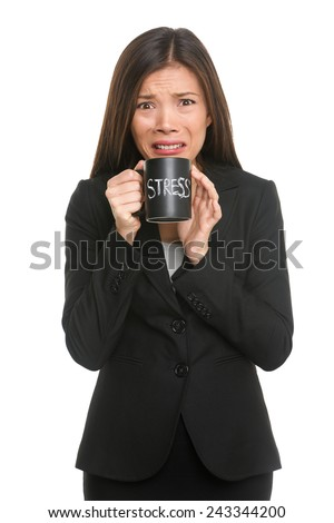 Stress. Business woman stressed being too busy. Businesswoman in suit holding head drinking coffee creating more stress. Mixed race Asian Caucasian female isolated on white background. - stock photo