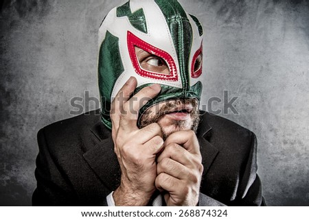 Stress, businessman angry with Mexican wrestler mask - stock photo