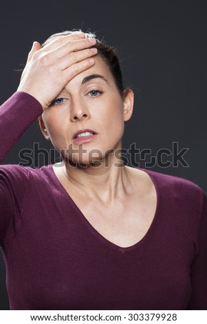 stress concept - anxious 30s woman with brown hair looking disappointed with her hand on forehead,studio shot