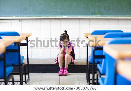 stress  girl sitting and  thinking on the classroom floor
