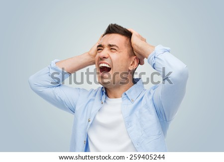 stress, headache, desperation, grief and people concept - unhappy man with touching his head and screaming over gray background - stock photo