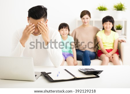 stress man calculating  bills while  family  sitting on the sofa - stock photo