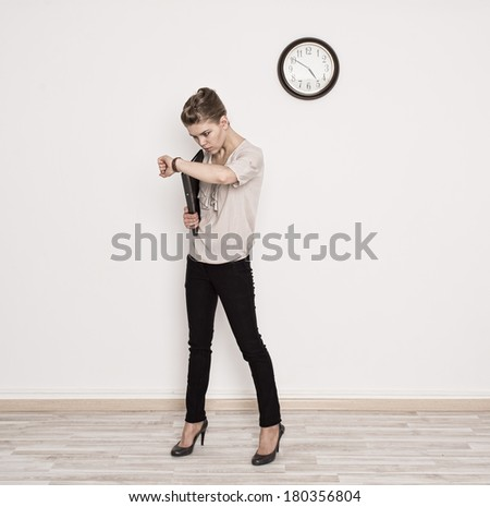 Stress. Rush time. Young woman looking at time in hurry. Full body portrait of young Caucasian lady carrying black folder at the office.   - stock photo