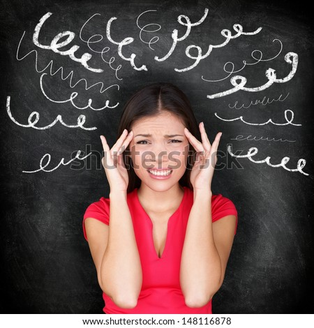 Stress - woman stressed with headache. Female stressed and worried with migraine headache pain. Blackboard concept with young female model on chalkboard black background. Asian Chinese / Caucasian. - stock photo