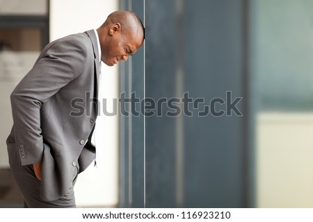 stressed african american businessman bang his head against wall - stock photo