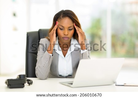 stressed african businesswoman sitting in office - stock photo