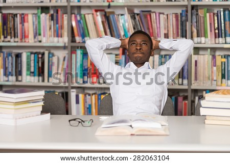 Stressed African Student Of High School Sitting At The Library Desk - Shallow Depth Of Field - stock photo
