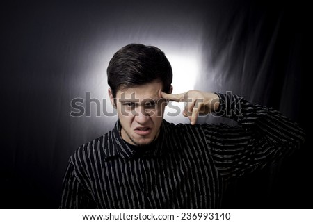 Stressed, aggressive portrait of a young student, man,pointing with finger to his had with harmful,mad look trying to remember something.Facial expression.Remember,memorizing. - stock photo