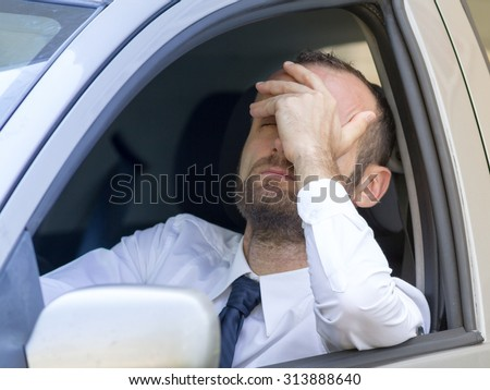 Stressed and furious driver in his car - stock photo
