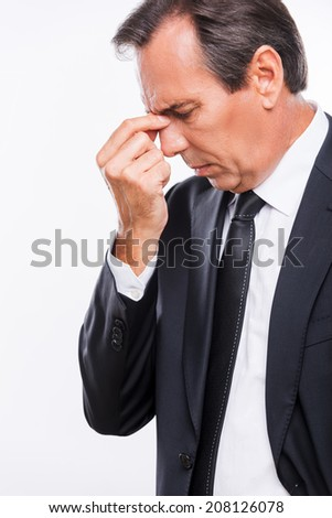 Stressed and overworked. Side view of frustrated young man in formalwear touching his nose with hand and keeping eyes closed while standing isolated on white background - stock photo