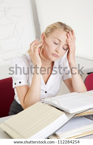 stressed and overworked  young businesswoman in the office - stock photo