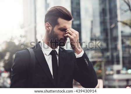Stressed and tired. Frustrated young man in formalwear massaging his nose and keeping eyes closed while standing outdoors with cityscape in the background - stock photo