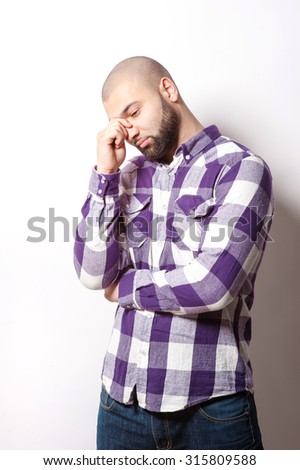 Stressed and tired. Young thoughtful Arabic man touching his head while standing against white background. - stock photo