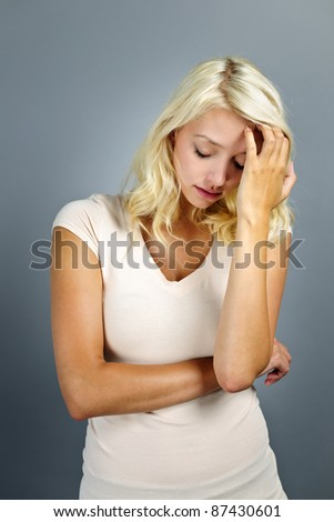 Stressed and worried young blonde woman on grey background - stock photo