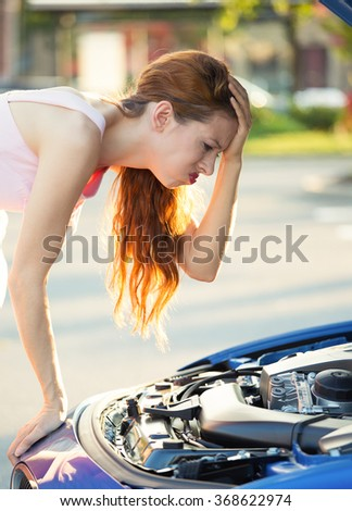Stressed, angry young woman in front of her broken down car with opened hood looking at engine, outside street, road. Negative face expressions, emotions, feelings. Bad luck, lemon car - stock photo