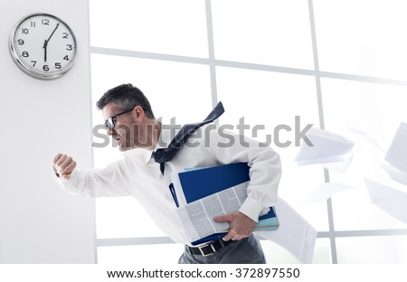 Stressed anxious businessman in a hurry checking time and running, he is late for his business appointment - stock photo