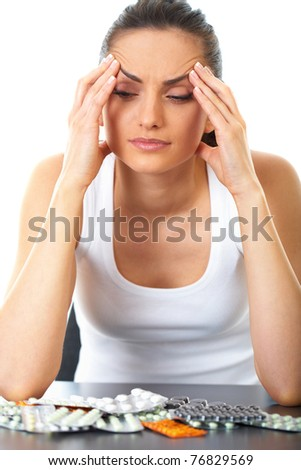 stressed attractive young brunette holds her head, some pills on the table in front of her, isolated on white - stock photo