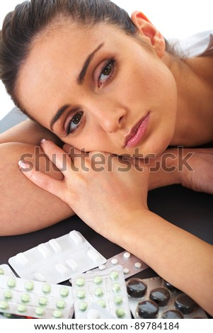 stressed attractive young brunette take some pills, isolated on white - stock photo