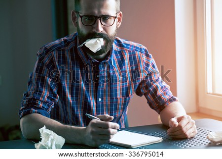 stressed bearded man writing with pen and making mistake or searching idea - stock photo