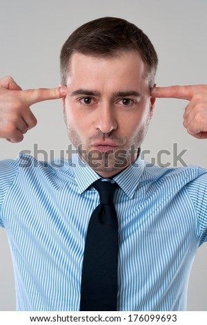 Stressed business man put fingers on face as gun isolated on grey background