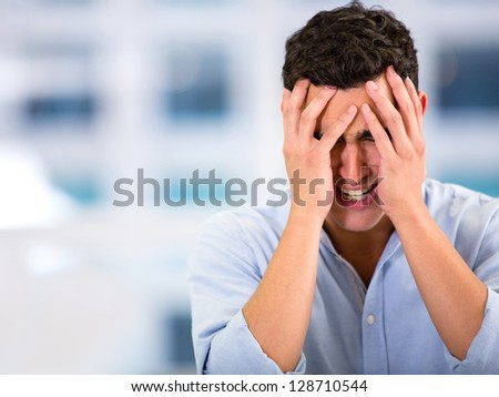 Stressed business man with a headache  at the office - stock photo
