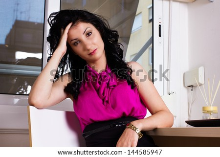 Stressed business woman at office, holding head with hand.