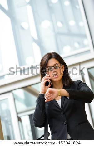 Stressed Business woman leaving corporate city building in a hurry looking time in her watch and talking on cellphone. Caucasian businesswoman working outside and being late for a business meeting. - stock photo
